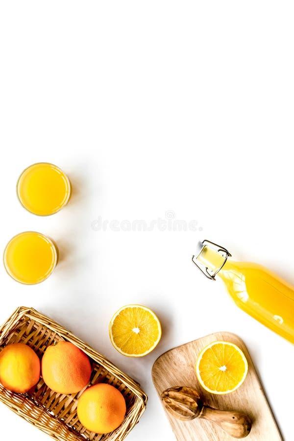 Frisch zusammengedrückter Orangensaft Juicer und Scheiben von Orangen auf weißem copyspace Draufsicht des Hintergrundes stockfotos