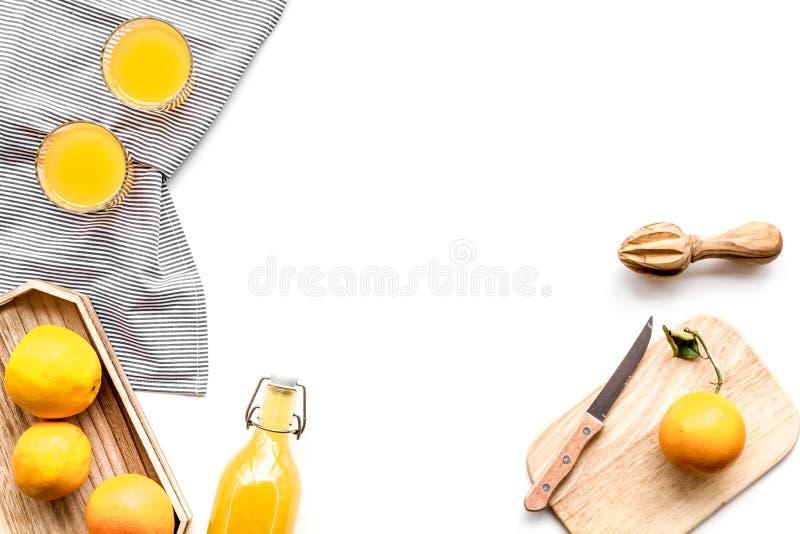Frisch zusammengedrückter Orangensaft Juicer und Scheiben von Orangen auf weißem copyspace Draufsicht des Hintergrundes stockbilder