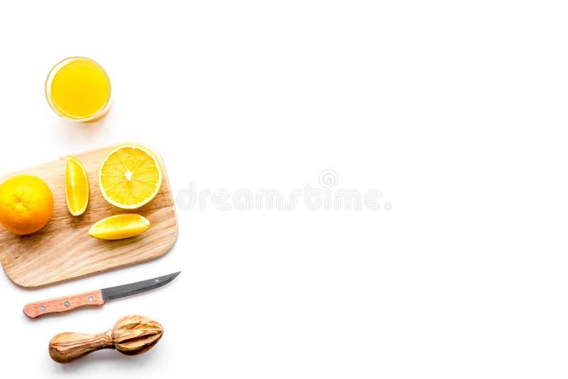 Frisch zusammengedrückter Orangensaft Juicer und Scheiben von Orangen auf weißem Draufsicht-Kopienraum des Hintergrundes stockfoto