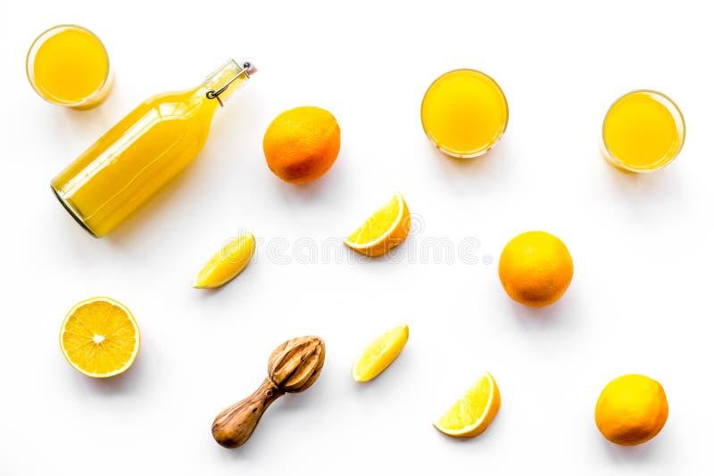 Frisch zusammengedrückter Orangensaft Juicer und Scheiben von Orangen auf weißem Muster copyspace Draufsicht des Hintergrundes lizenzfreie stockfotos