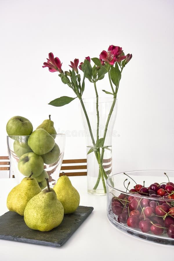Frische Äpfel und Birnen nahe zum Vase Kirschen auf dem Tisch lizenzfreie stockfotos
