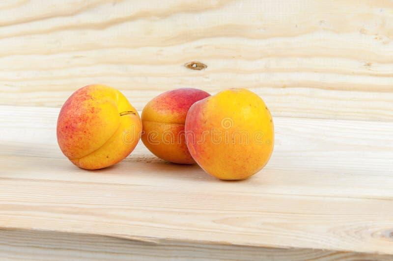 Frische Aprikosen auf hölzernem Hintergrund lizenzfreie stockfotos