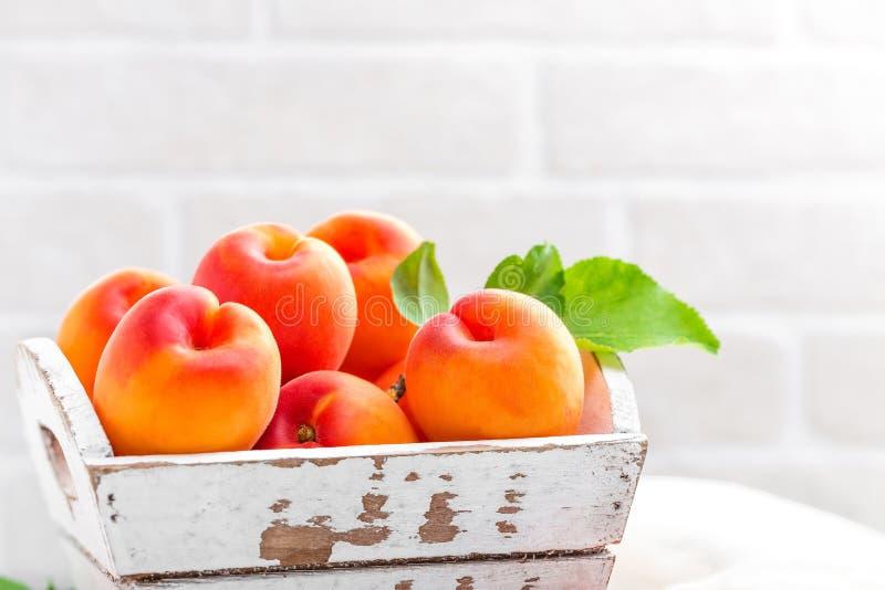 Frische Aprikosen mit Blättern auf weißem hölzernem Hintergrund stockfoto
