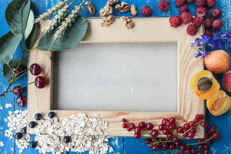 Frische Beeren und Früchte auf einem Hintergrund des Segeltuches, der Aprikose, der Kirschen, der Himbeeren und der Korinthen stockbild