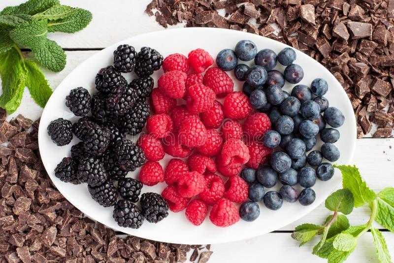 Frische Beeren und zerquetschte dunkle Schokolade stockbilder