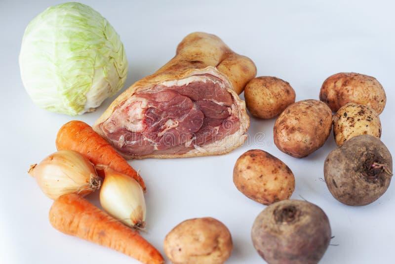 Frische Bestandteile für Borscht: Kartoffeln, Kohl, rote Rübe, Karotten, Schweinefleischbein und Zwiebel auf weißem Hintergrund stockbilder