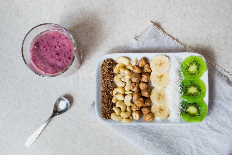 Frische Bestandteile für eine gesunde rohe Nahrungsmittelfrühstück Kiwi, Kokosnussflocken, Acajoubäume und Haselnüsse geschossen  stockbild