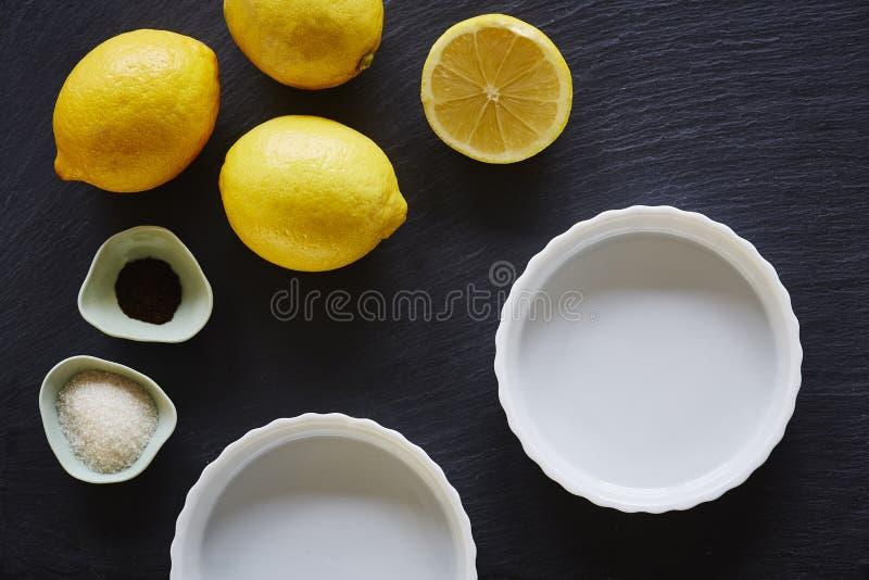 Frische Bestandteile für Zitronentorte foodie Backen auf Schiefer Countertop stockfotos