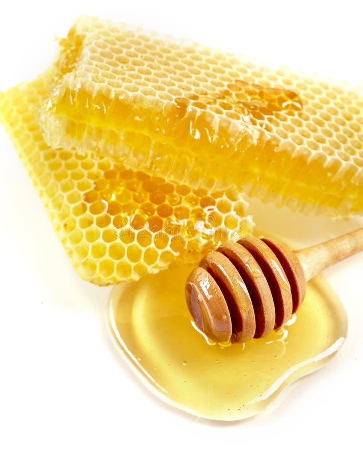 Frische Bienenwabe mit einem hölzernen Schöpflöffel lizenzfreie stockfotografie