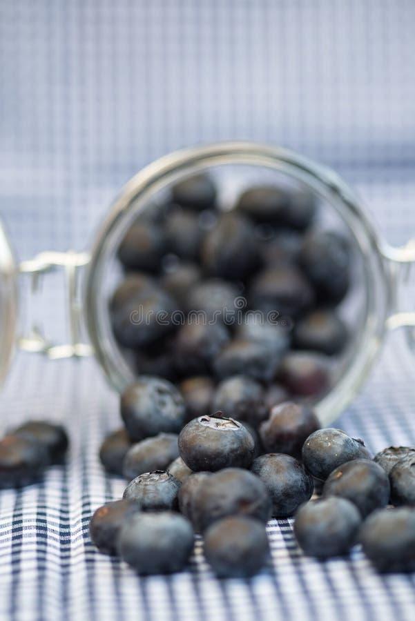 Frische Blaubeeren, die aus Glasgefäß heraus fallen lizenzfreie stockfotos
