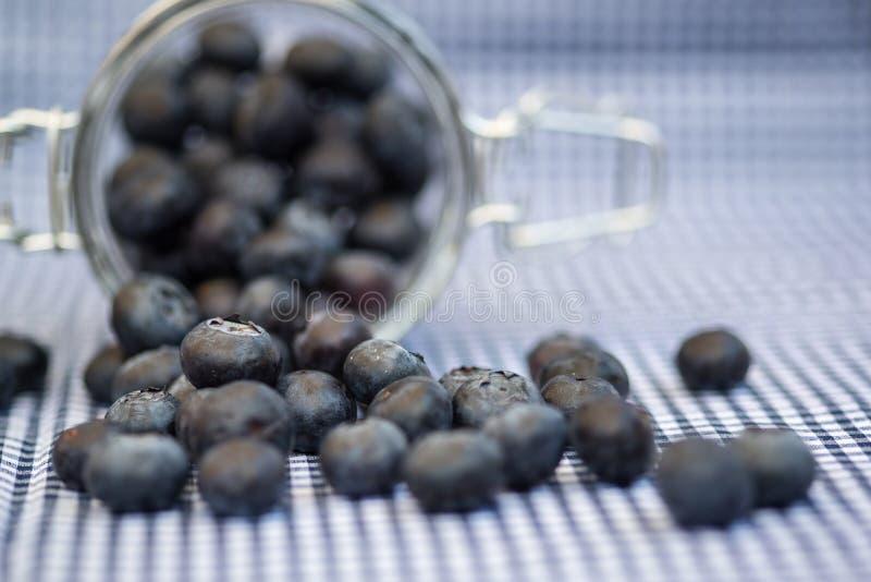 Frische Blaubeeren, die aus Glasgefäß heraus fallen stockbilder
