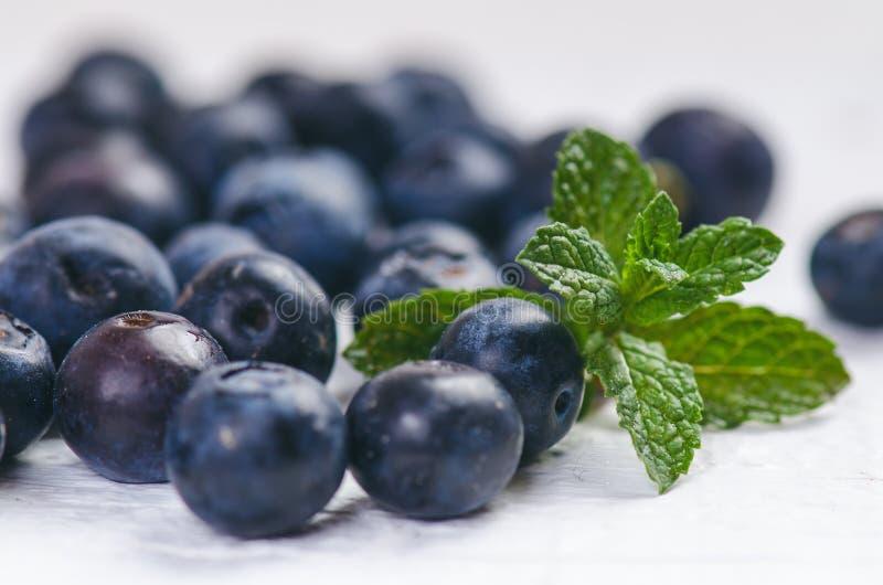 Frische Blaubeeren mit Minze auf einer hölzernen weißen Tabelle natürliches Antioxydant Konzept der gesunden Nahrung Organisches  lizenzfreie stockfotografie
