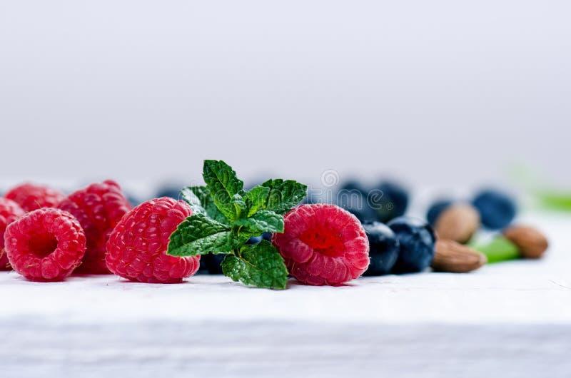 Frische Blaubeeren mit Minze auf einer hölzernen weißen Tabelle natürliches Antioxydant Konzept der gesunden Nahrung Organisches  lizenzfreies stockbild