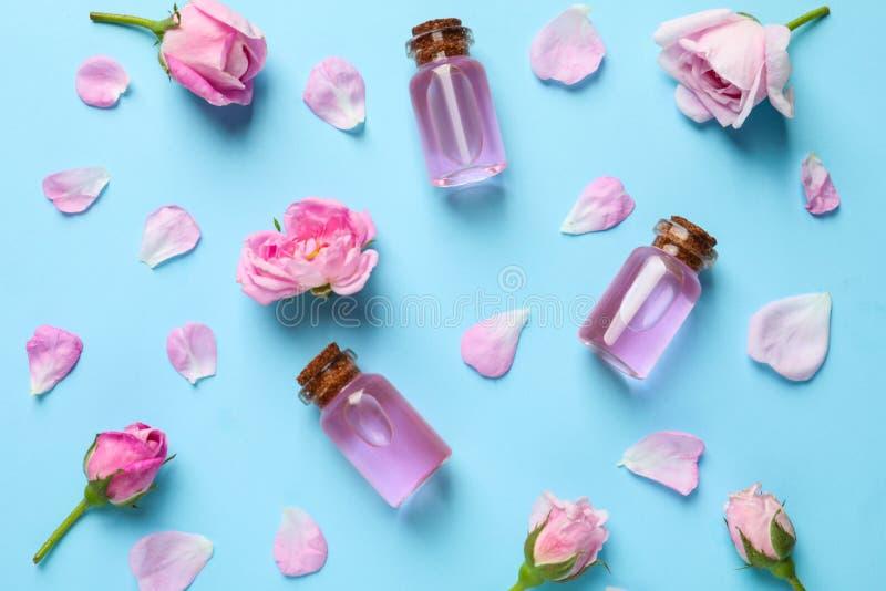Frische Blumen, Blumenblätter und Flaschen rosafarbenes ätherisches Öl auf Farbhintergrund lizenzfreie stockfotografie