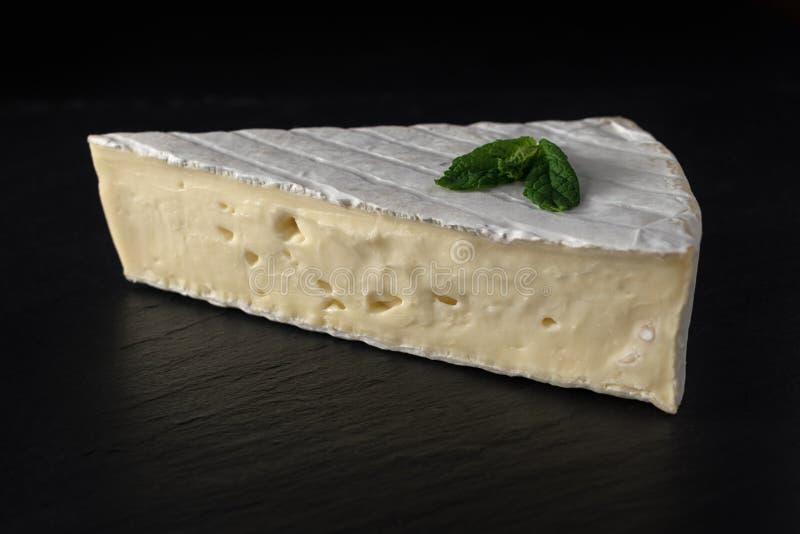 Frische Brie auf Steinbrett mit Kräutern lizenzfreie stockfotografie