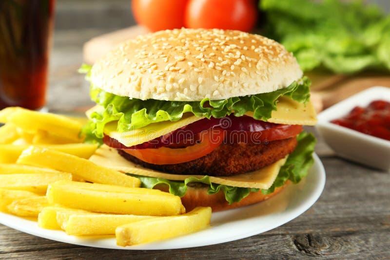 Frische Burger auf Platte auf einem grauen hölzernen Hintergrund stockbild