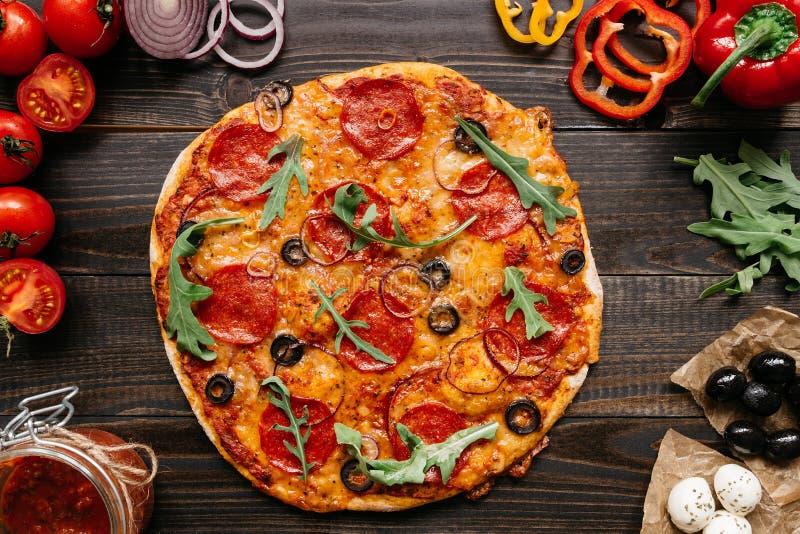 Frische delisious Pizza mit Pizzabestandteilen auf dem Holztisch, Draufsicht lizenzfreies stockbild