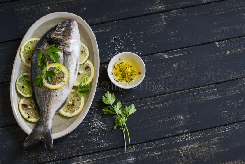 Frische Dorado-Fische mit Zitrone, Kalk und Petersilie auf einem ovalen Teller stockbilder