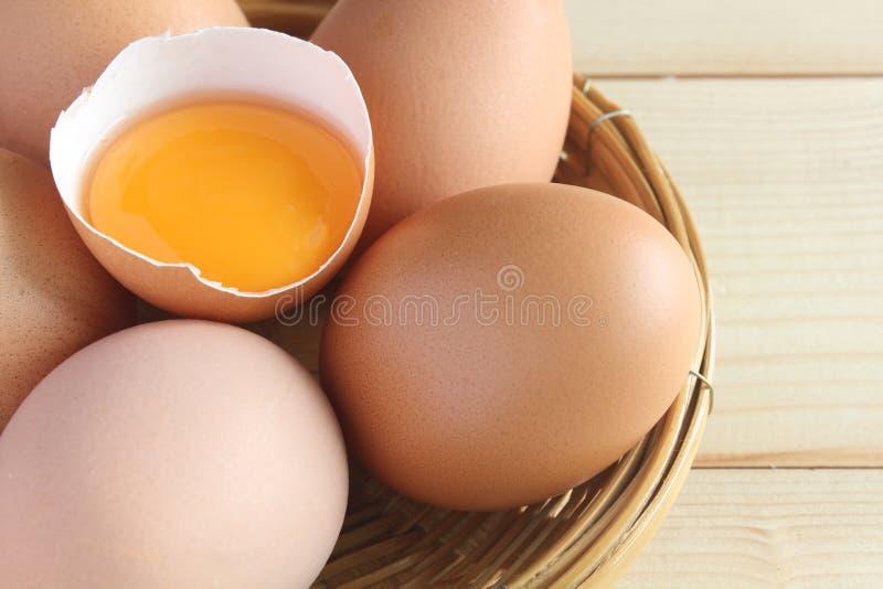 Frische Eier und Eigelb in den Oberteilen im Korb lizenzfreie stockfotos