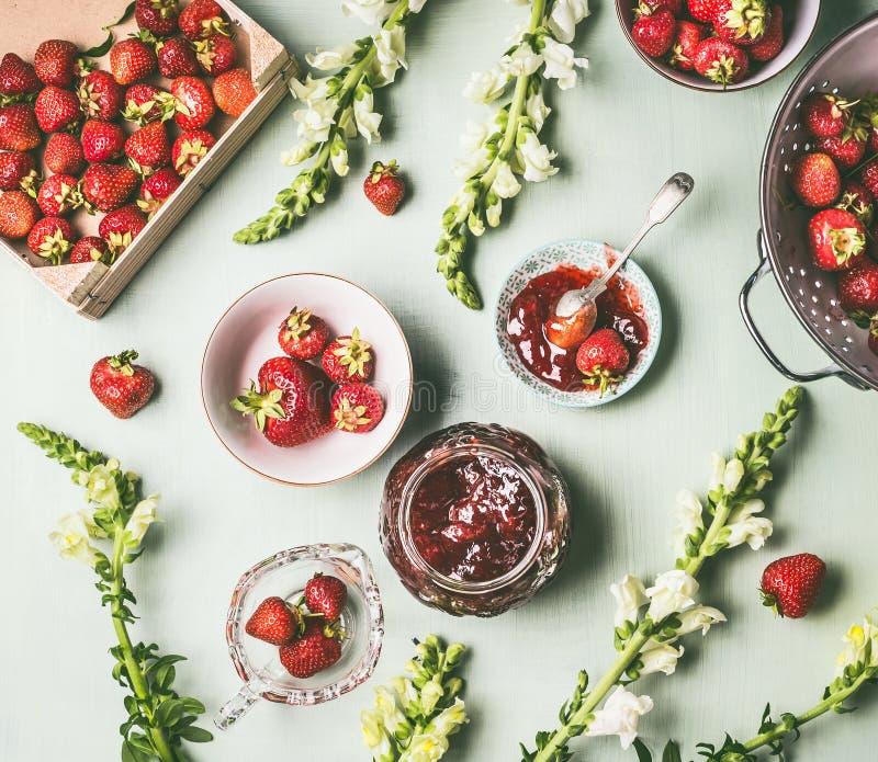 Frische Erdbeeren der flachen Lage im hölzernen Sieb und in den Schüsseln mit Stauglas und -löffel auf Küchentischhintergrund mit lizenzfreies stockfoto
