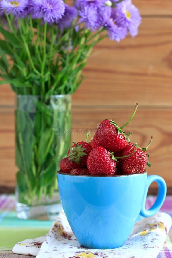 Frische Erdbeeren in einem blauen Cup stockbilder