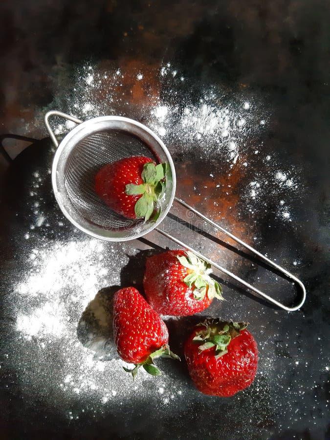 Frische Erdbeeren in einem kleinen Metallsieb mit pulverisiertem Puderzucker auf einem dunklen Hintergrund stockbild
