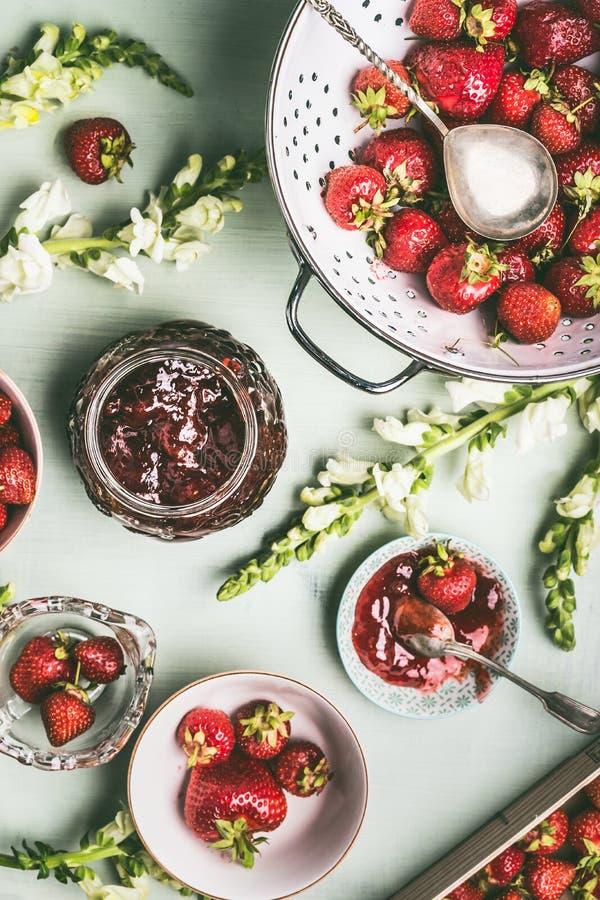 Frische Erdbeeren im Sieb und in den Schüsseln mit Stauglas und -löffel auf Küchentischhintergrund mit Gartenblumen, Draufsicht S lizenzfreie stockbilder