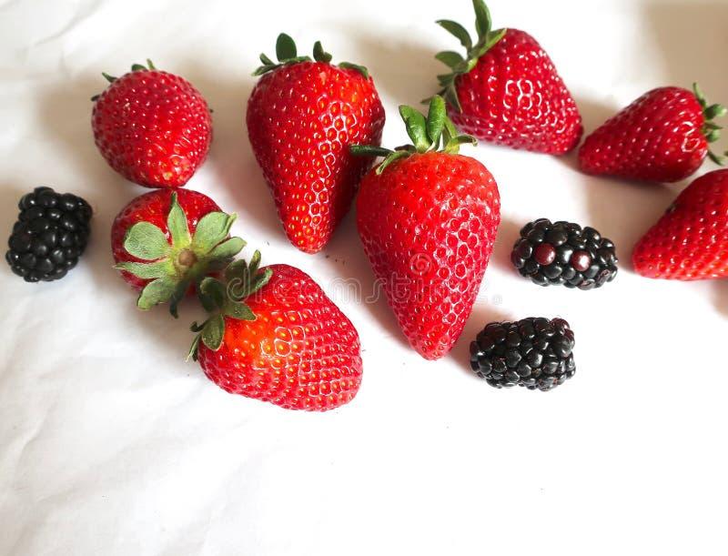 Frische Erdbeeren und Brombeeren auf einem weißen Hintergrund stockfotografie