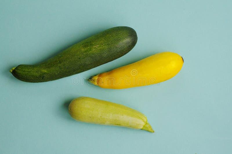 Frische farbige Zucchini drei auf einem blauen Hintergrund lizenzfreie stockbilder
