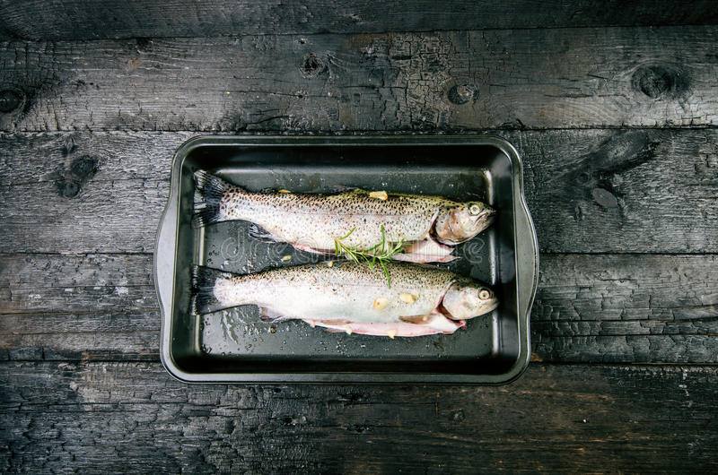 Frische Fische auf einem Weinleseschwarzen, gebrannte Tabelle Hölzerne Tabelle Fischen Sie mit Gemüse, Salz, Öl, Kräuter Konzept  lizenzfreie stockfotos