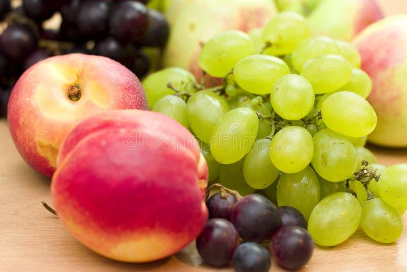 Frische Früchte, Äpfel, Trauben und Pfirsiche stockbild
