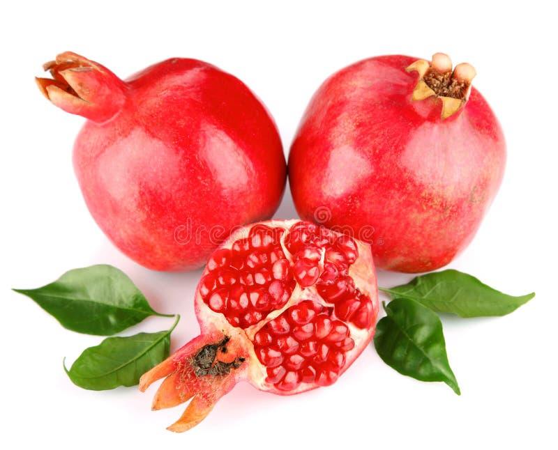 Frische Früchte des Granatapfels mit grünen Blättern stockfoto