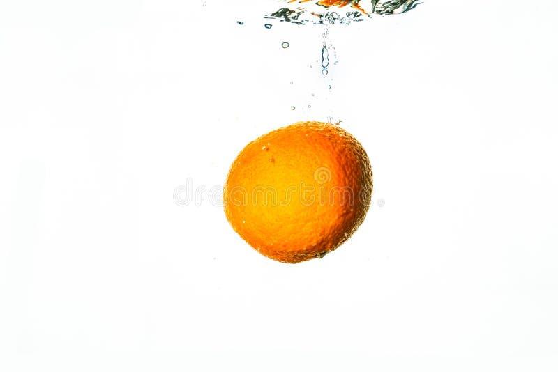 Frische Frucht fällt in Wasser mit weißem Hintergrund stockbilder