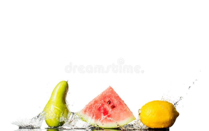 Frische Frucht im Wasserspritzen mit dem Kopienraum lokalisiert auf weißem Hintergrund lizenzfreie stockfotos