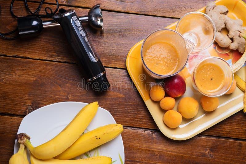 Frische Frucht Smoothie mit Banane und Aprikosen am orange Behälter mit Mischmaschine am Holztisch Flache Lage stockfotografie
