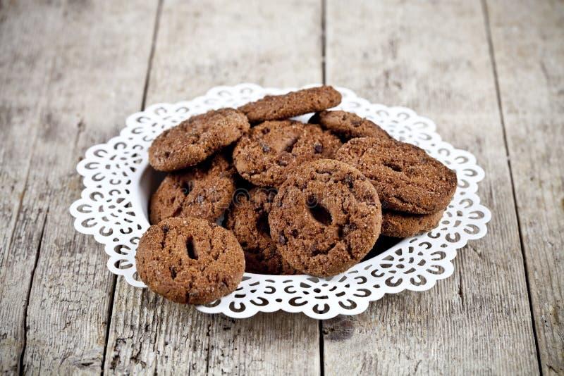 Frische gebackene Schokoladensplitterpl?tzchen h?ufen auf wei?es plateon rustikalem Holztisch stockfotografie