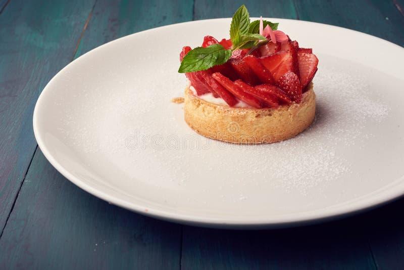 Frische gebackene selbst gemachte Torte mit Erdbeeren und Schlagsahne und Zimt auf weißer Platte Nahaufnahme Spitze oder obenlieg stockfoto