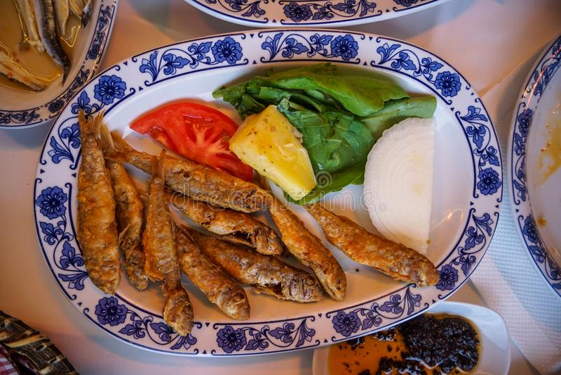 Frische gebratene kleine Fische mit gebratener Kartoffel, grünem Salat, Tomate und Zwiebel auf weißer ovaler Platte mit blauem Mu lizenzfreies stockfoto