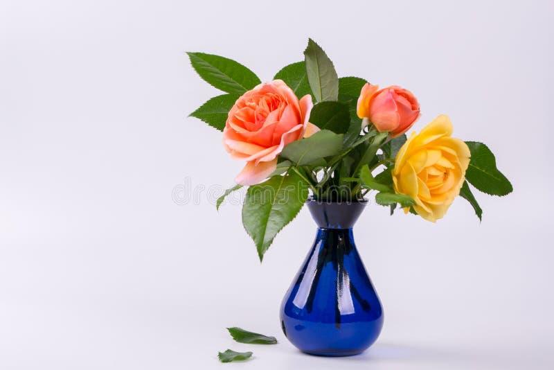 Frische Gelb- und Pfirsichrosen in einem blauen Vase lizenzfreie stockbilder