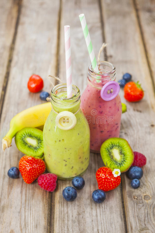 Frische gemischte Frucht Smoothies in den WeinleseMilchflaschen stockbilder