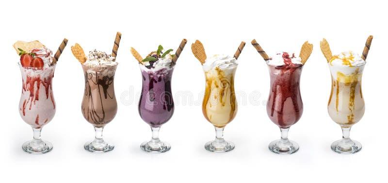 Frische geschmackvolle Cocktails, Gläser mit köstlichen Milchshakes lokalisiert auf Weiß lizenzfreies stockbild