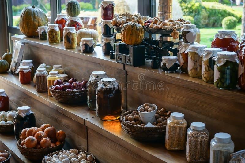 Frische geschmackvolle Kürbise und konserviertes und in Essig eingelegtes Saisongemüse und Honig in den Glasgefäßen und auf Körbe stockfotografie