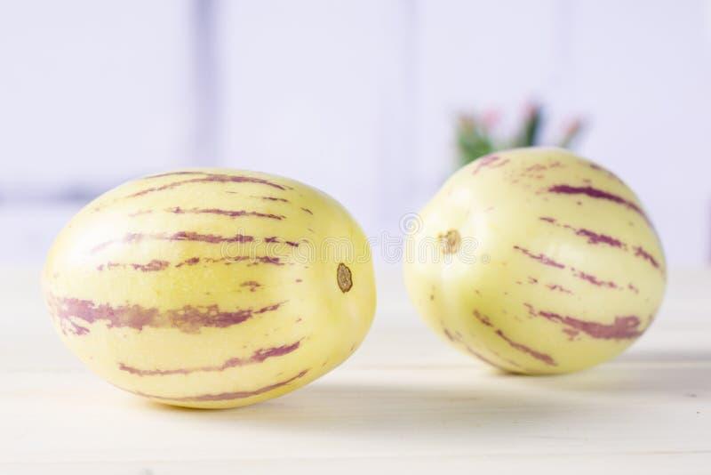 Frische gestreifte pepino Melone mit roten Tulpen stockbild