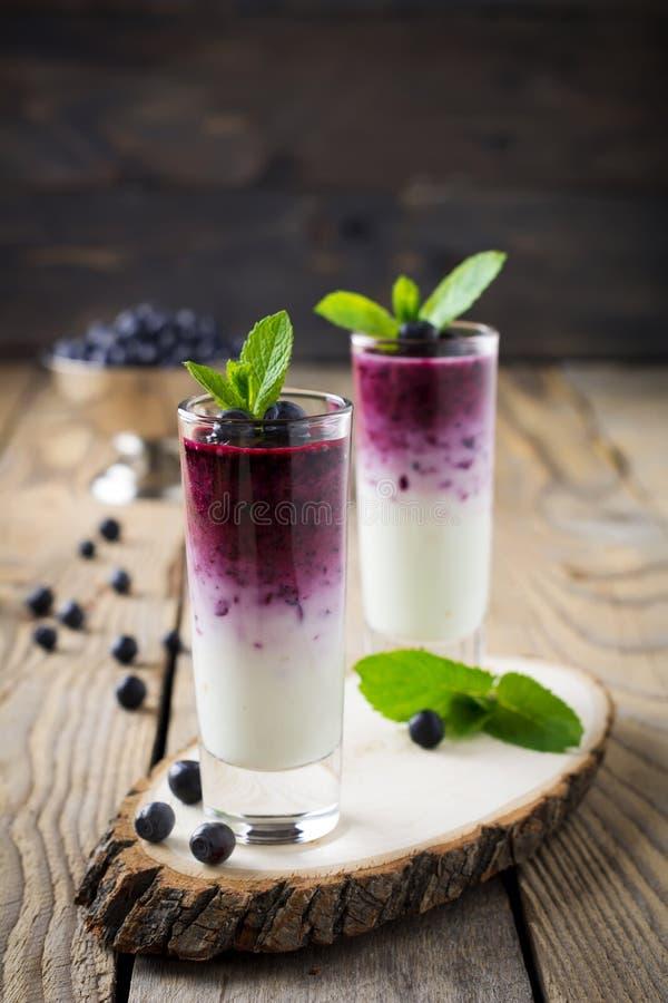 Frische gesunde Blaubeerensmoothies in einem Glas mit Beeren und tadellosen Blättern auf einem hölzernen Stand stockfotos