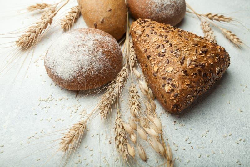 Frische, gesunde ganze Körner des Roggens und des Weißbrots, besprühtes Mehl für Sackleinen und eine rustikale weiße Tabelle, Nah lizenzfreie stockfotografie