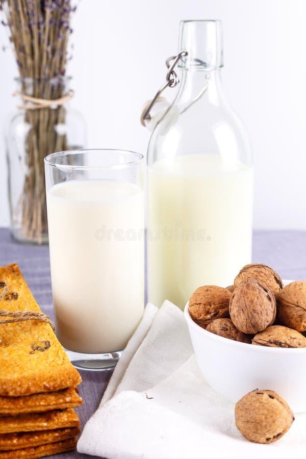 Frische gesunde Milch, Plätzchen mit Rosinen, Walnüsse, Bündel Trockenschnittlavendel auf weißem Hintergrund Selektiver Fokus stockbild