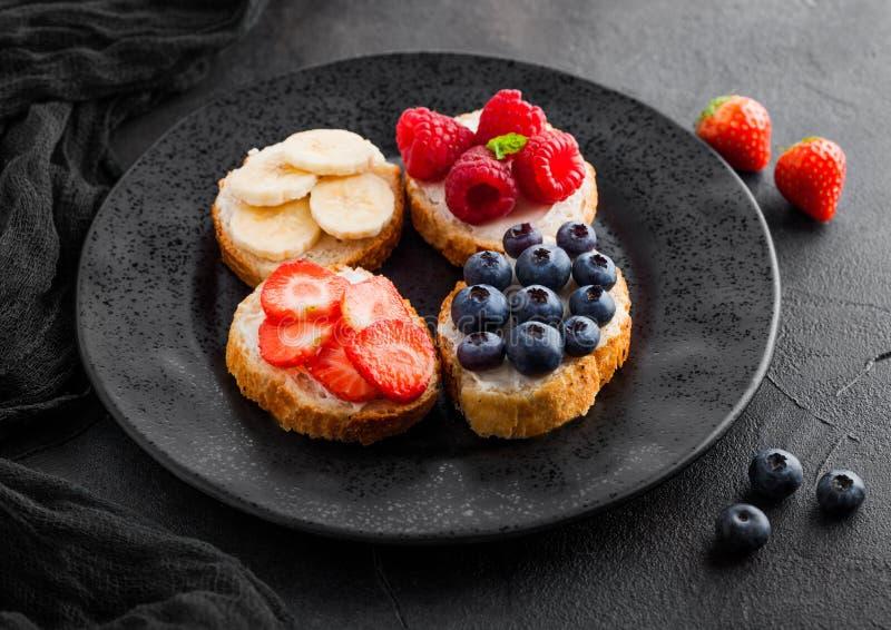 Frische gesunde Minisandwiche mit Sahne Käse, Früchte und Beeren im Schwarzblech mit Stoff Erdbeeren, Blaubeeren, Bananen lizenzfreie stockfotos