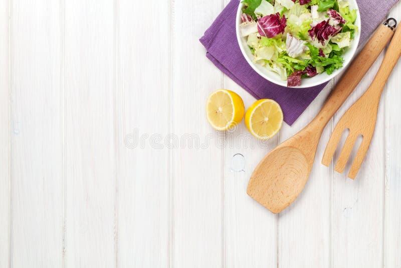 Frische gesunde Salat- und Küchengeräte stockbilder