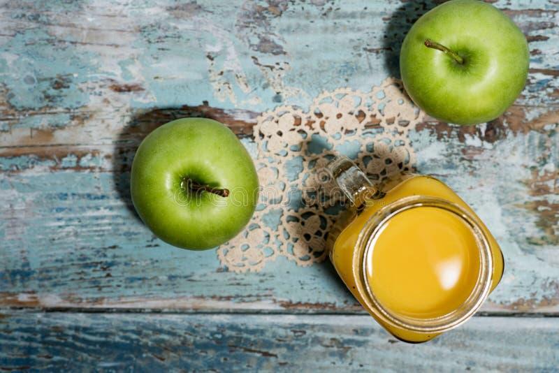 Frische grüne Äpfel und ein Glas frischer Orangensaft stockbild