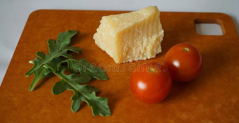 Frische grüne Arugulablätter, Kirschtomaten und Parmesankäseparmesankäse auf Hartfaserplatte stockfotografie